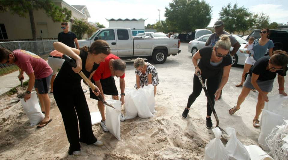 Residents work together to fill sandbags for each other at Bobby Hicks Park as residents prepare for Hurricane Irma on Tuesday in Tampa, Florida.