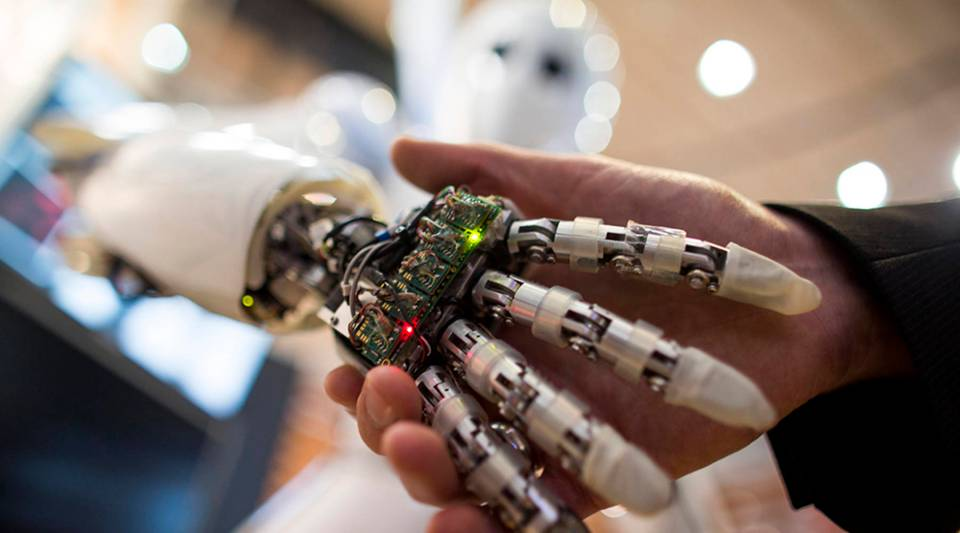 A visitor holds a hand of an AILA, or Artificial Intelligence Lightweight Android.