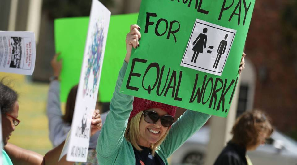 A woman joins with other protesters to ask that woman be given the chance to have equal pay as their male co-workers on March 2017 in Fort Lauderdale, Florida.