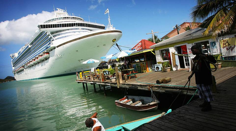 Fishermen tie up their wooden boat next to a cruise liner in St John's, Antigua.