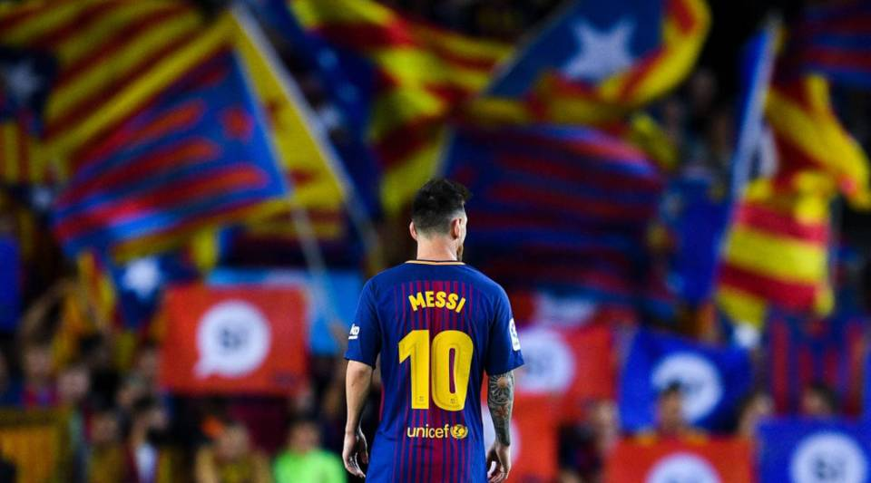 Lionel Messi of FC Barcelona looks on as Catalan Pro-Independence flags are seen on the background during the La Liga match between Barcelona and SD Eibar at Camp Nou on September 19, 2017 in Barcelona, Spain.
