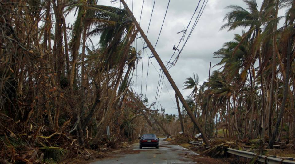 A car drives under tilted power line poles in the aftermath of Hurricane Maria in Humacao, Puerto Rico, on Oct. 2.