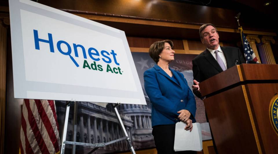 Sen. Amy Klobuchar, a Democrat from Minnesota, looks on as Democratic Sen. Mark Warner of Virginia introduces the Honest Ads Act on Capitol Hill on Oct. 19. The legislation is designed to increase the transparency of political ads on social media platforms like Twitter and Facebook.