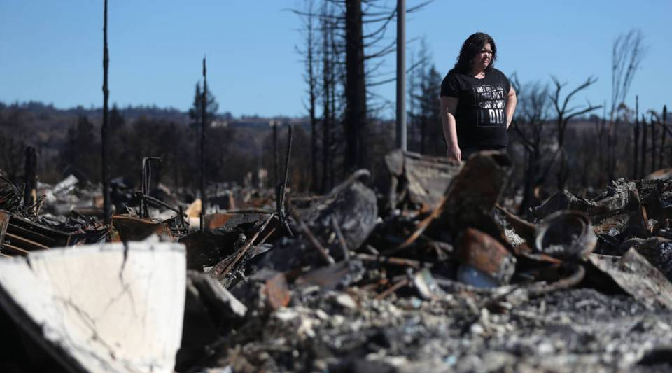 Renee Hernandez looks over the remains of her Coffey Park home that was destroyed by the Tubbs Fire on Oct. 23 in Santa Rosa, California.
