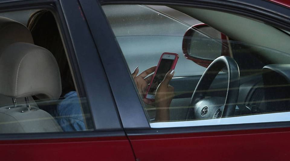 A driver uses a phone while behind the wheel of a car in New York City.