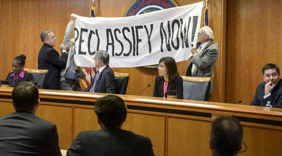 Commissioner Mignon Clyburn, Chairman Tom Wheeler, Commissioner Jessica Rosenworcel and Commissioner Michael O'Rielly watch as protesters are removed from the dais during a hearing at the Federal Communication Commission on Dec. 11, 2014. in Washington, D.C.