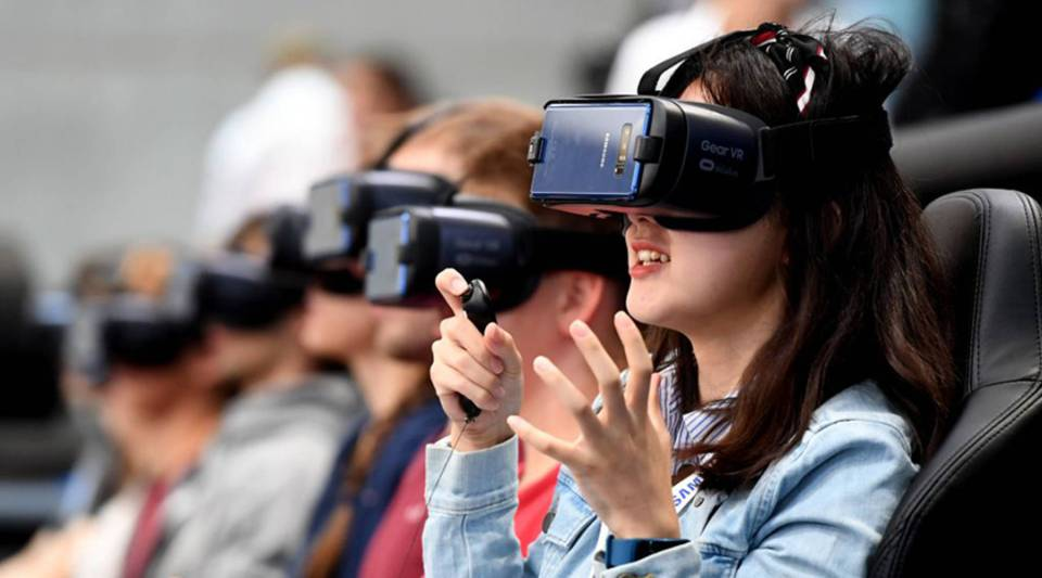 Visitors try out VR glasses at the booth of Samsung at the IFA Consumer Electronics Fair in Berlin on September 2, 2017.