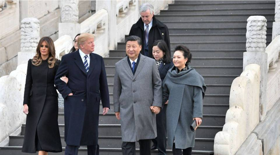 President Donald Trump, walking with first lady Melania Trump, looks at China's President Xi Jinping and his wife, Peng Liyuan, as they tour the Forbidden City in Beijing today.
