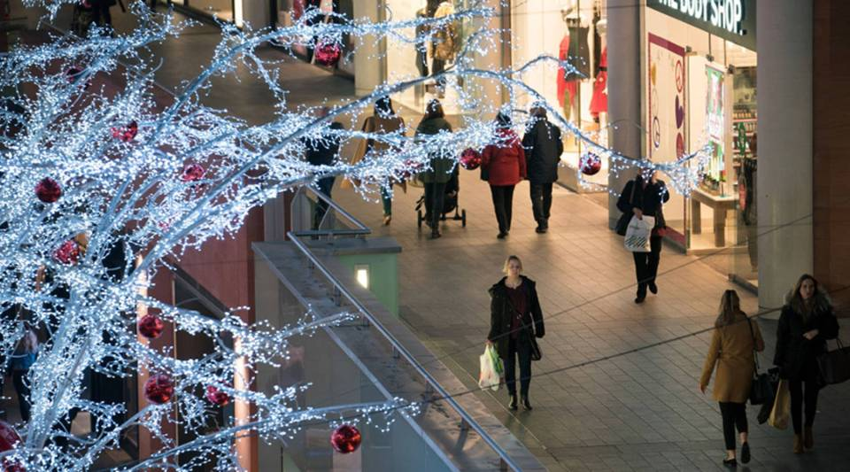 Shoppers walk among the Christmas lights in a mall.