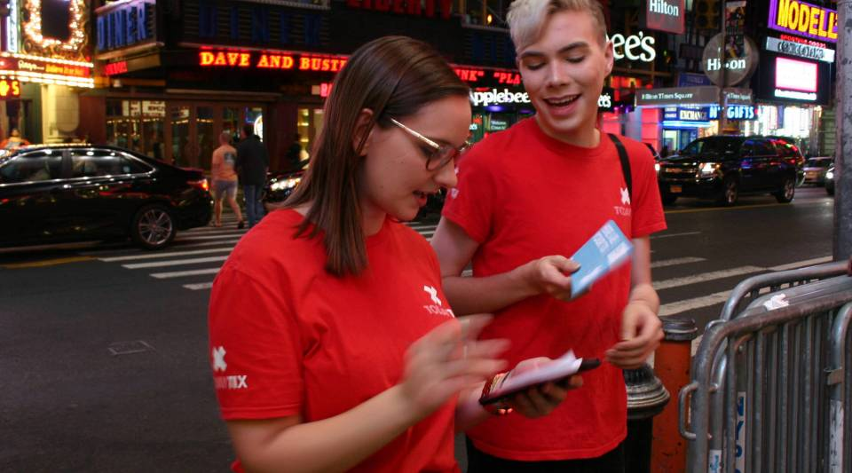 Katie Szajkovics and Christoper Huey, two of TodayTix concierges, stand outside the theater and distribute tickets to customers.