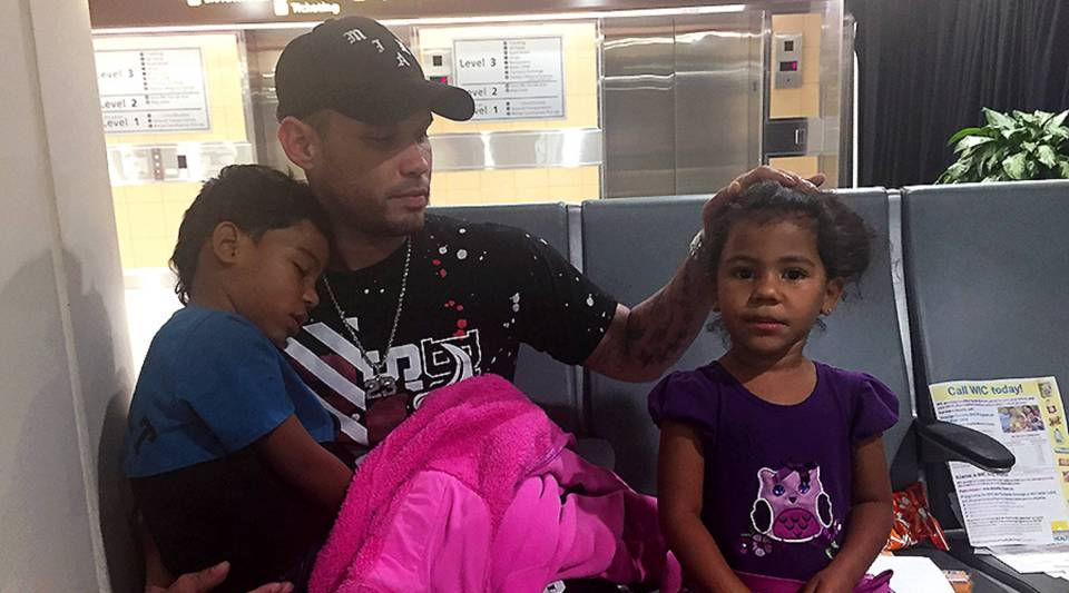 Jonathan Gonzalez waits with his children outside the Hurricane Maria Relief Center in Orlando, Florida.
