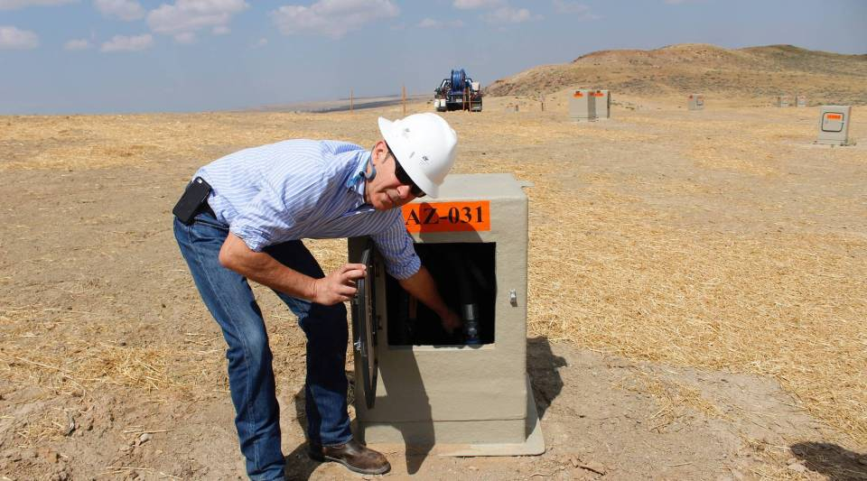 Nichols Ranch Manager Bernard Bonifas reaches into one of the hundreds of tan boxes dotting the landscape at the Nichols Ranch uranium mine. They keep injection and recovery wells insulated during Wyoming's harsh winters.