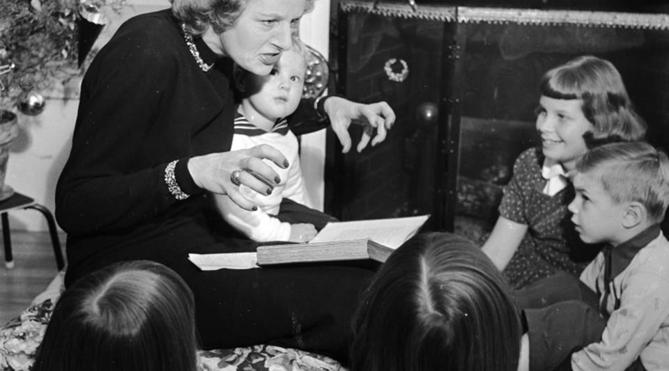 """Circa 1954,English novelist and magazine columnist Monica Dickens reads to her children from """"A Christmas Carol"""" by her grandfather Charles Dickens."""