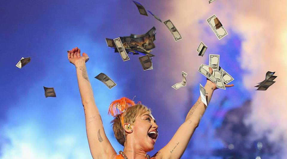 Miley Cyrus throws money in the air as she performs at the opening night of her Bangerz Tour in Australia at Rod Laver Arena on October 10, 2014 in Melbourne, Australia.