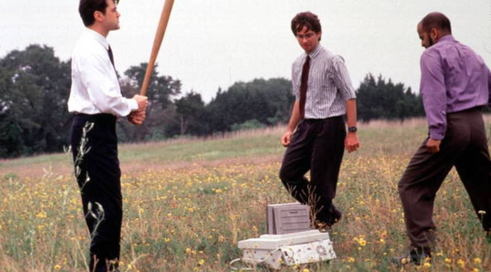 "In a scene from ""Office Space,"" Ron Livingston, left, David Herman and Ajay Naidu take their revenge on the office fax machine."