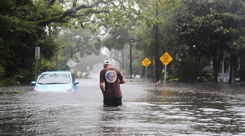 A man walks through a flooded street as Hurricane Matthew passes through St. Augustine, Florida, on Oc. 7, 2016. The storm caused flooding in Virginia also.