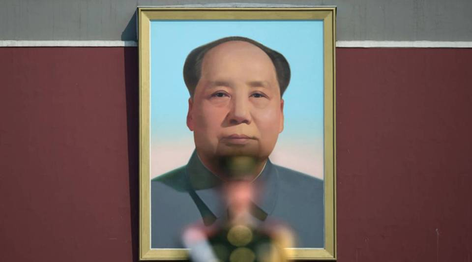 A paramilitary police officer stands guard in front of a portrait of the late communist leader Mao Zedong in Beijing.