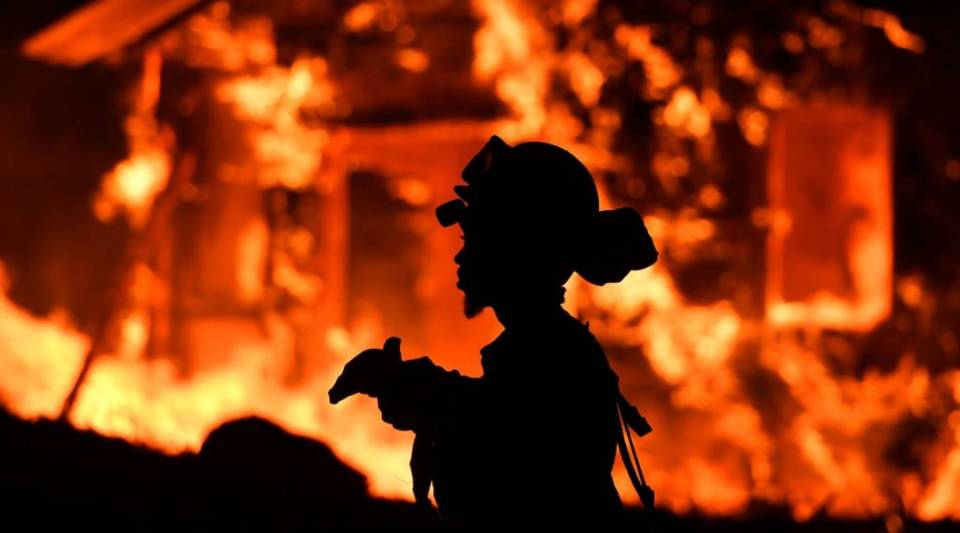 An inmate firefighter monitors flames as a house burns in the Napa wine region in California on October 9, 2017, as multiple wind-driven fires continue to whip through the region.