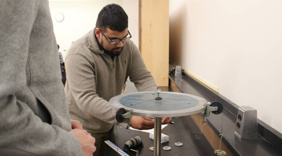 Freshman Phillip Parent lines up metal weights in an introductory physics class at the University of Maine at Machias. The class is part of a partnership between the state's universities.