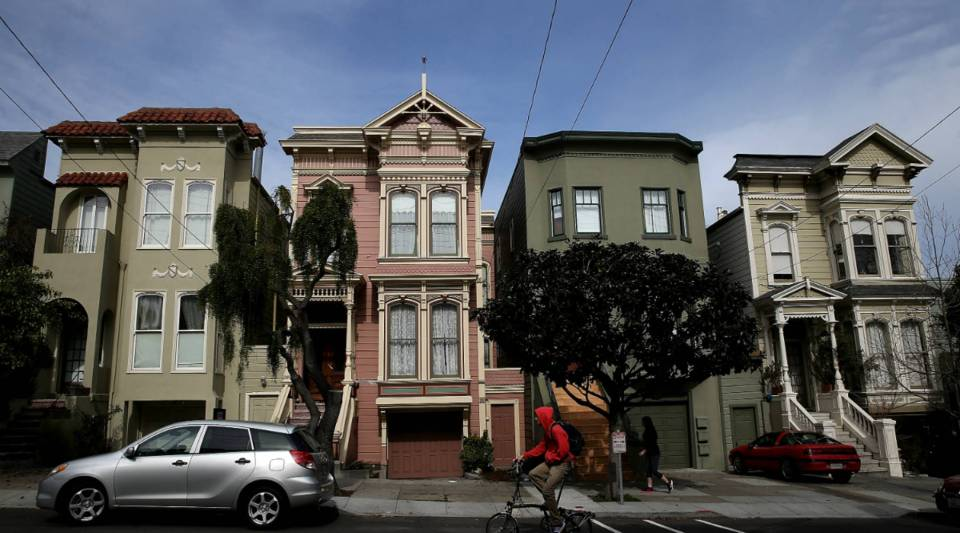A bicyclist rides by a row of homes in San Francisco, California.