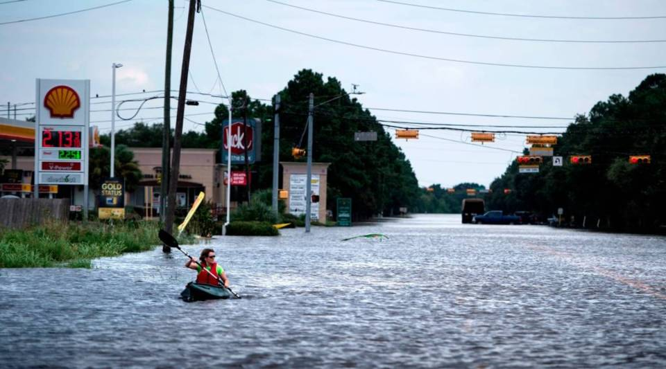 A woman paddles down a flooded road while shuttling deliveries for her neighbors during the aftermath of Hurricane Harvey on Aug. 30, 2017 in Houston, Texas.