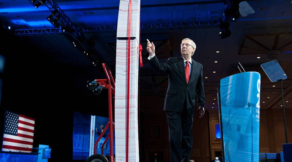 U.S. Senate Minority Leader Mitch McConnell points to a stack of papers representing what he said are the regulations associated with former President Barack Obama's health care reform as he speaks at the Conservative Political Action Conference in National Harbor, Maryland, in 2013.