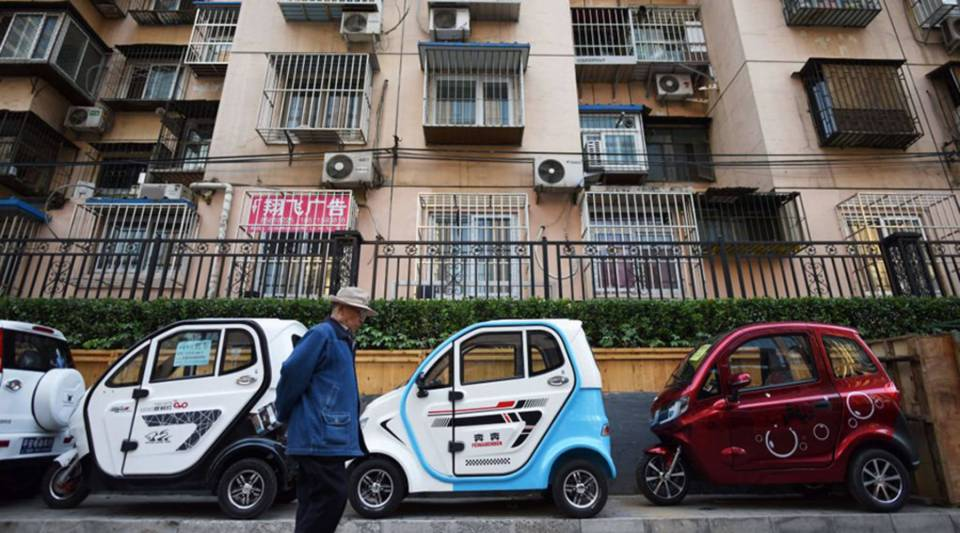 A man walks past electric cars and tricycles on a sidewalk in Beijing in 2017.