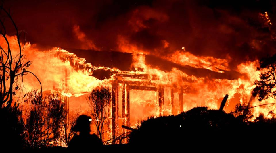 Firefighters assess the scene as a house burns in the Napa wine region of California on Oct. 9, 2017.