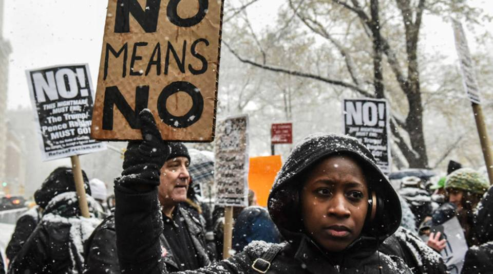 People carry signs addressing the issue of sexual harassment at a #MeToo rally outside of Trump International Hotel on Dec. 9, 2017 in New York City.