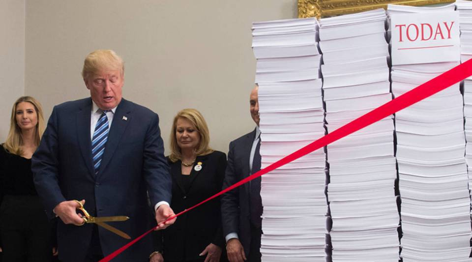 President Donald Trump cuts red tape tied between two stacks of papers representing the government regulations of the 1960s, left, and the regulations of today at the White House on Dec. 14, 2017.