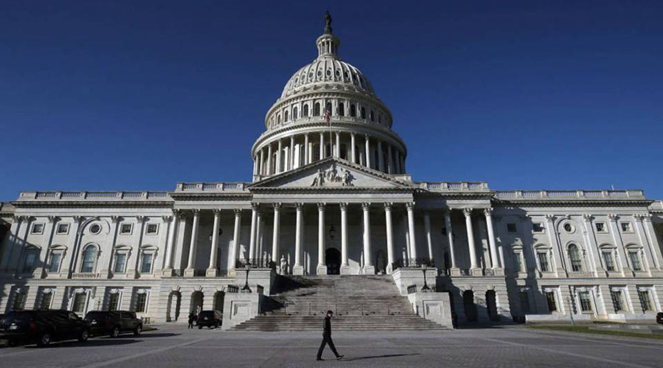 A pedestrian walks past the U.S. Capitol as congressional lawmakers work on a deal to fund the government and avert a shutdown by midnight Friday, on Dec. 21, 2017 in Washington, D.C.