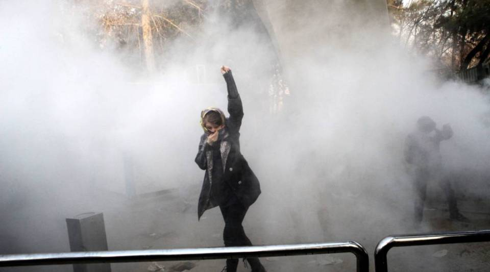 An Iranian woman raises her fist amid the smoke of tear gas at the University of Tehran during a protest in the capital on Dec. 30. Students protested in the third day of demonstrations sparked by anger over Iran's economic problems.