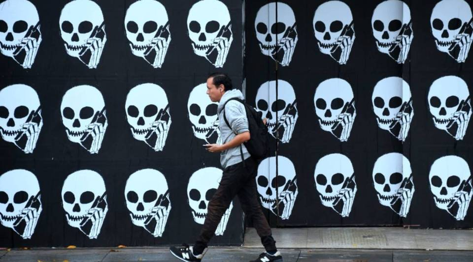 A pedestrian using his cellphone walks past a boarded establishment showing skeleton heads with cellphones in Los Angeles in January.
