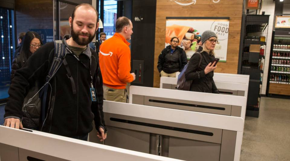Shoppers scan the Amazon Go app on their mobile devices as the enter the store Monday in Seattle. Amazon opened the cashier-less store to the public after more than a year in beta.