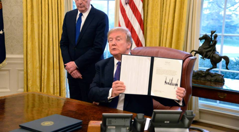 President Donald Trump displays a Section 201 action as US Trade Representative Robert Lighthizer witnesses, in the Oval Office, at the White House, January 23, 2018, in Washington, DC. The administration is issuing tariffs on imported solar panels and washing machines to protect American manufacturing companies against dumping by foreign countries, mainly China, and including South Korea.