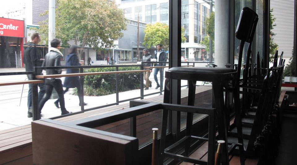 Empty chairs in the recently closed bar, Cantine in Seattle's South Lake Union, look out at neighborhood workers with lunch takeout containers. The bar and several other restaurants closed this year because of lackluster dinner patronage.