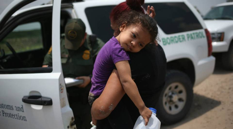 A mother and child, 3, from El Salvador await transport to a processing center for undocumented immigrants after they crossed the Rio Grande into the United States in Mission, Texas.