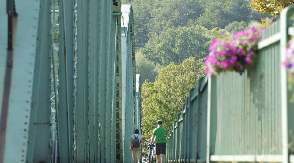 Cyclists cross a bridge over the Youghiogheny River, veering off the Great Allegheny Passage, to check out downtown West Newton.
