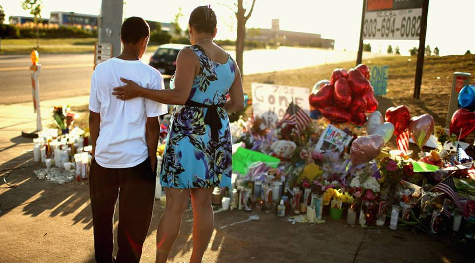 Barb Whitfield (R) and her grandson Wanya Whitfield, 15, visit at a makeshift memorial to the victims of the mass shooting at the Century 16 movie theater July 22, 2012 in Aurora, Colorado.