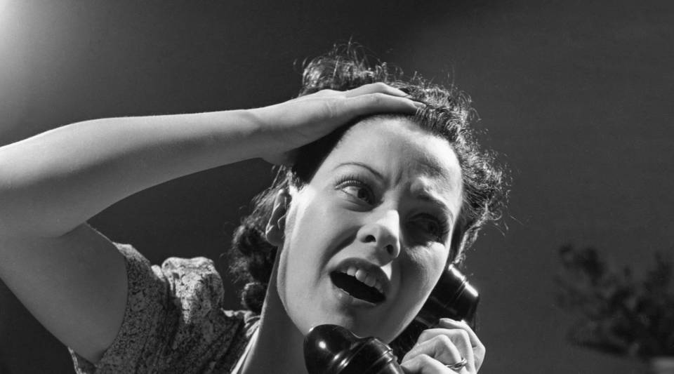 An exasperated woman cries for help on the phone, circa 1940.