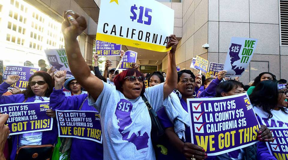 Workers celebrate outside the Ronald Reagan State Building in downtown Los Angeles on April 4, 2016, after California Gov. Jerry Brown signed a bill that will raise the state's minimum wage to $15 an hour by 2022.