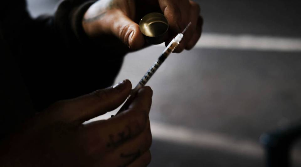 A man uses heroin under a bridge where he lives with other addicts in the Kensington section of Philadelphia, which has become a hub for heroin use.
