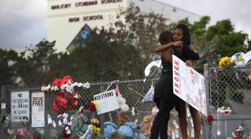 Tyra Heman (R) a senior at Marjory Stoneman Douglas High School, is hugged by Rachael Buto in front of the school where 17 people that were killed during a mass shooting in Parkland, Florida.