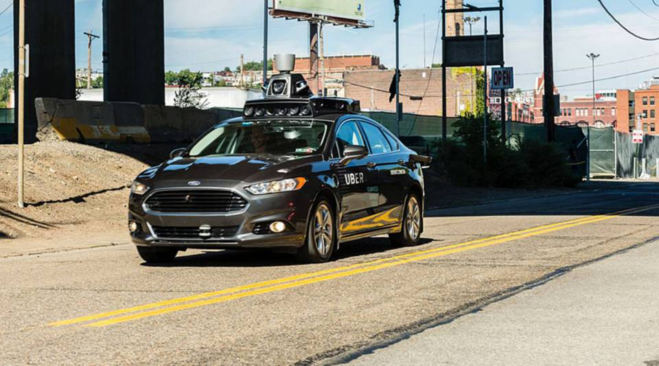 A passenger looks on as he rides in a pilot model of an Uber self-driving car on in 2016 in Pittsburgh, Pennsylvania.