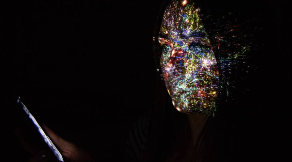 In this photo illustration, a virtual map of the internet is projected onto a woman in London.