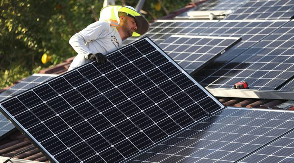 Andres Hernandez, from the Goldin Solar company, installs a solar panel system on the roof of a home a day after the Trump administration announced it will impose duties of as much as 30 percent on solar equipment made abroad on January 23, 2018 in Palmetto Bay, Florida.