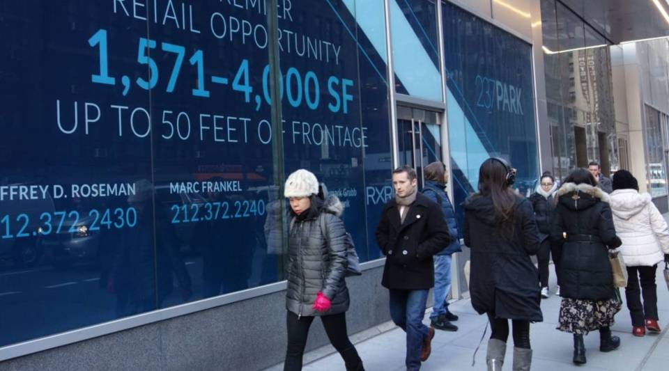 Pedestrians walk by a building advertising available retail space on Lexington Avenue on February 8, 2018 in New York.