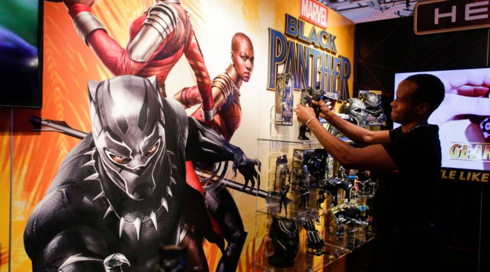 An exhibitor organizes 'Black Panther' items at the Hasbro showroom during the annual New York Toy Fair, on February 20, 2018, in New York. Toys and accessories linked to the movie, which is also making waves for its strong black female leading roles, have the potential to become an enduring presence in stores, like Spider-Man and other iconic figures, company executives say.