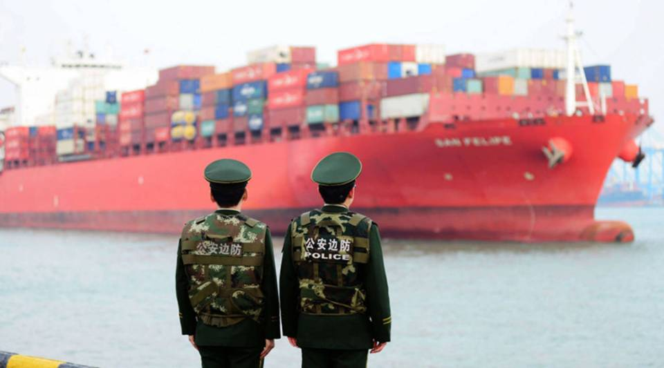 Chinese police officers watch a cargo ship at a port in Qingdao in China's eastern Shandong province on March 8, 2018.