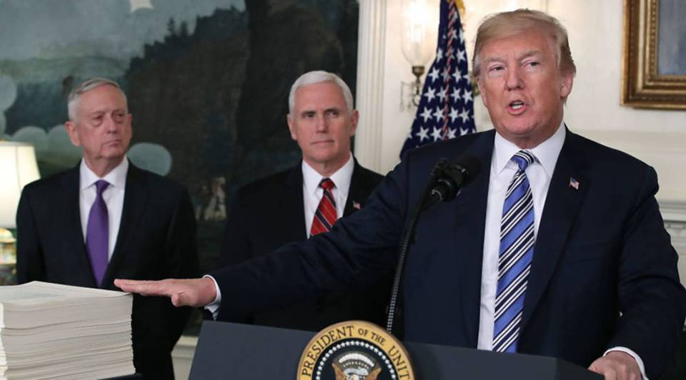 President Donald Trump gestures to the $1.3 trillion spending bill passed by Congress early Friday, with Vice President Mike Pence, center, and Defense Secretary Jim Mattis, left, at the White House.